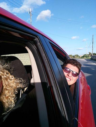 Happy Woman In Car Against Sky