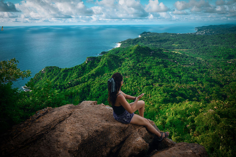 Woman on top of rock  by tropical jungle against sky