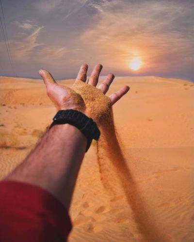 Cropped Hand Of Man Falling Sand At Desert Against Sky During Sunset