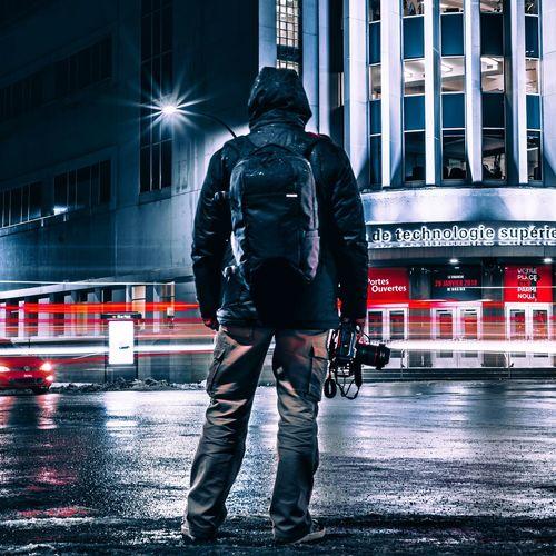 Rear view of man with umbrella on street in rainy season