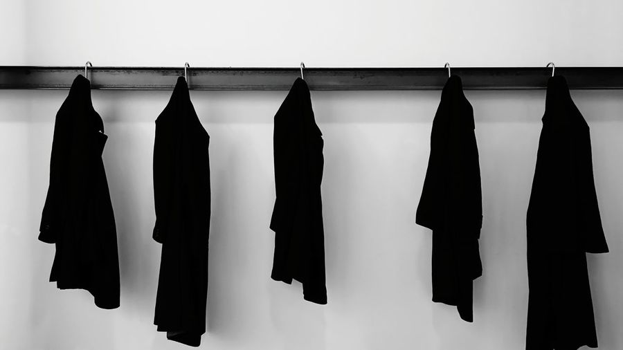 Low angle view of clothes hanging against white wall