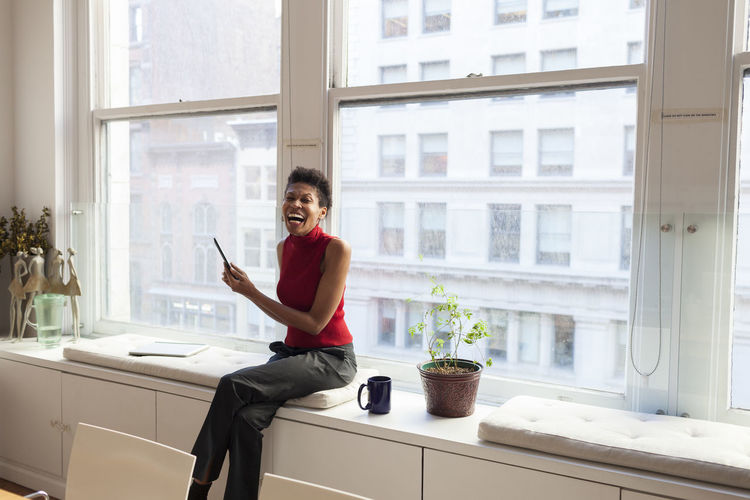 Businesswoman sitting on a windowsill