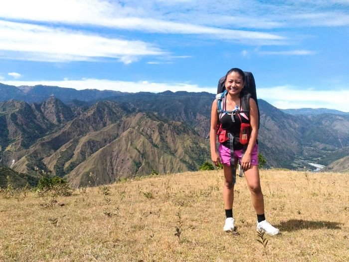 Full length of smiling young woman standing on mountain against sky