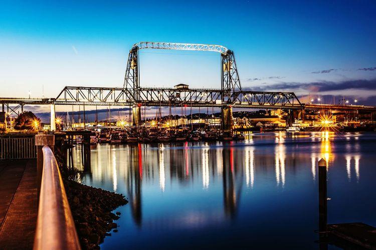 Bridge Over Harbor Against Illuminated Buildings At Sunset