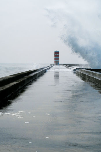 big wave of the atlantic ocean crushing over the walkway in front of lighthouse in porto, portugal Waves Dangerous Waterfront Water Crushing Nature Powerful Overflooded Flood Weather Storm Tsunami Porto Portugal Walkway Leading Line Water Sea Lighthouse Harbor Sky Horizon Over Water Building Exterior Analogue Sound