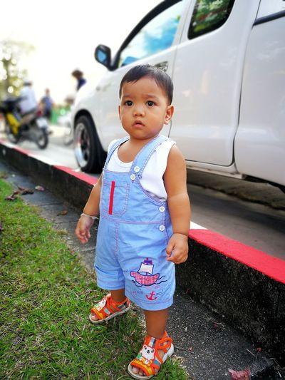 Cute girl standing on car