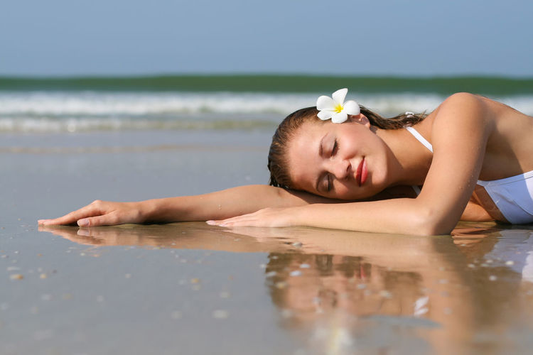 Portrait of young woman relaxing on beach