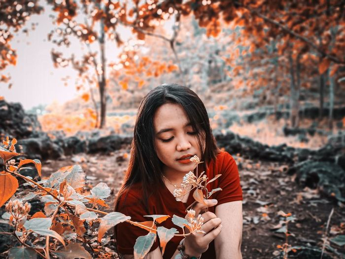 Young woman looking away while standing on tree during autumn