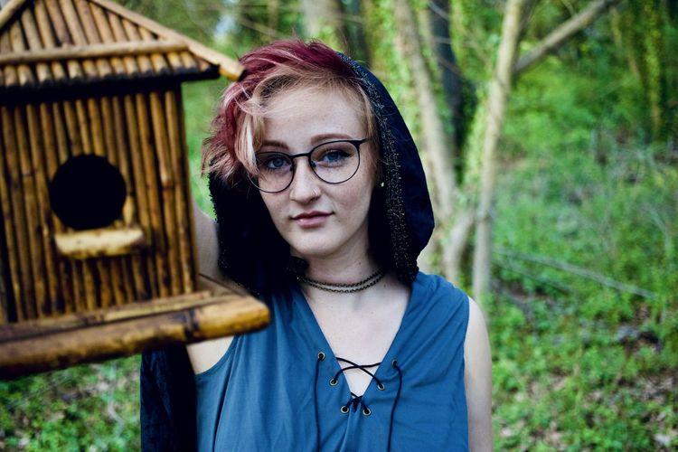 Portrait of woman with birdhouse