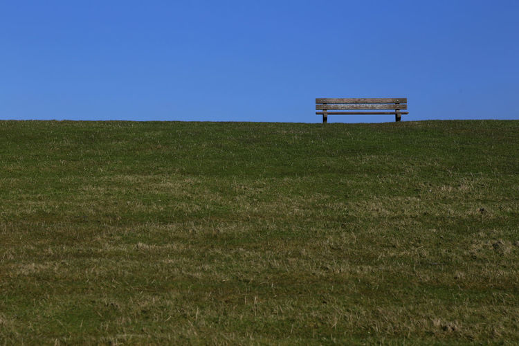1704, A bench on the dike Beauty In Nature Bench Blue Clear Sky Copy Space Day Dike Field Grass Green Color Growth Idyllic Landscape Nature No People North Sea Outdoors Scenics Sea Sky Tranquil Scene Tranquility