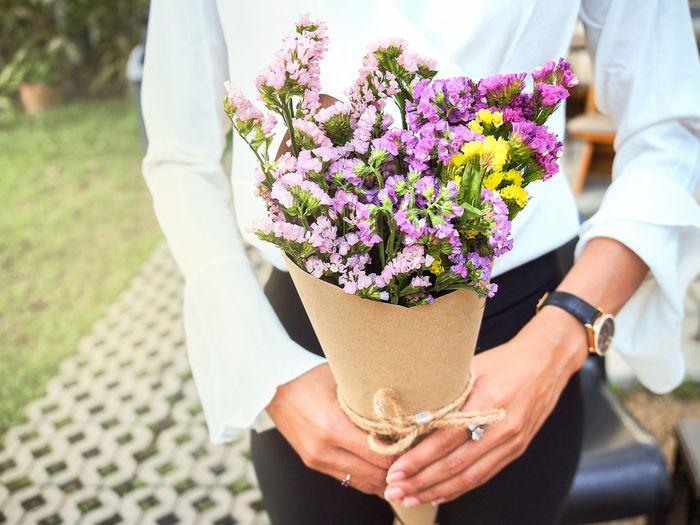 Midsection of businesswoman holding bouquet outdoors