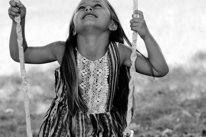 Portrait Of Smiling Girl On Swing