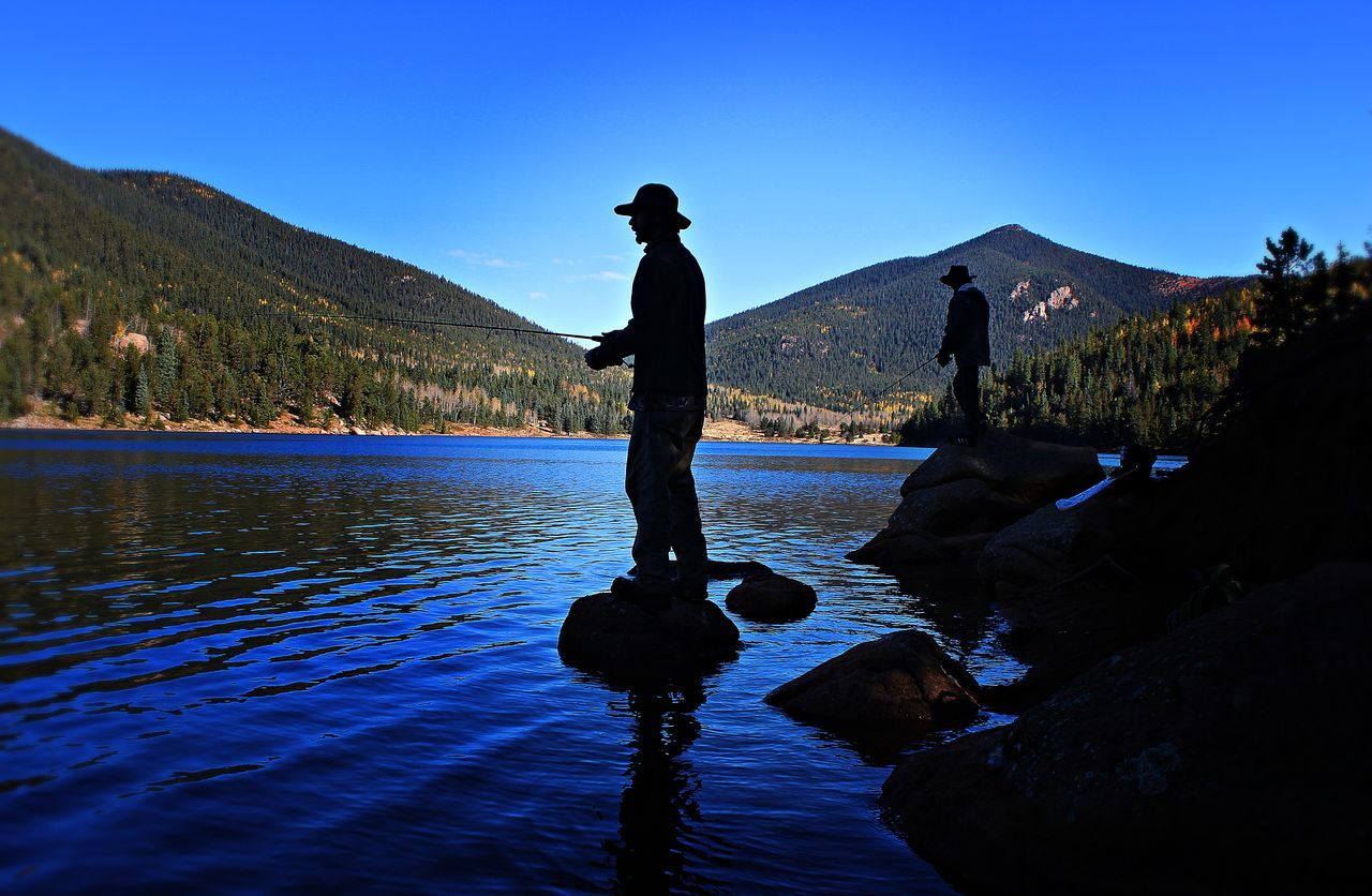 Silhouette man fishing in river against blue sky