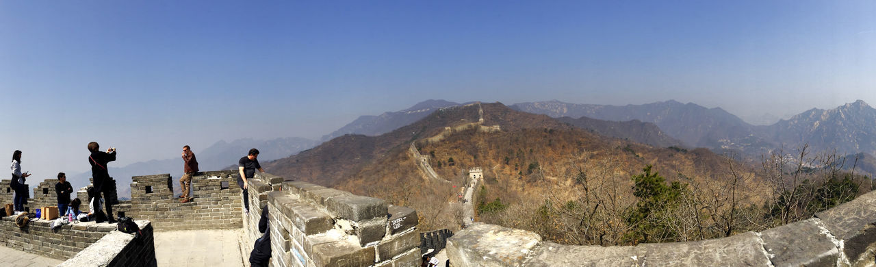 People standing on great wall of china against clear blue sky