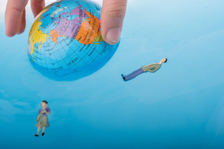 Close-up of hand holding globe by toys floating on water