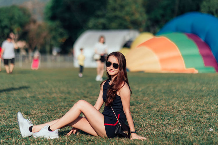 Fashion Sunglasses Glasses Young Adult One Person Focus On Foreground Smiling Women Hairstyle Adult Beauty Long Hair Full Length Young Women Brown Hair Happiness Grass Leisure Activity Hair Beautiful Woman Outdoors Hot Air Balloons