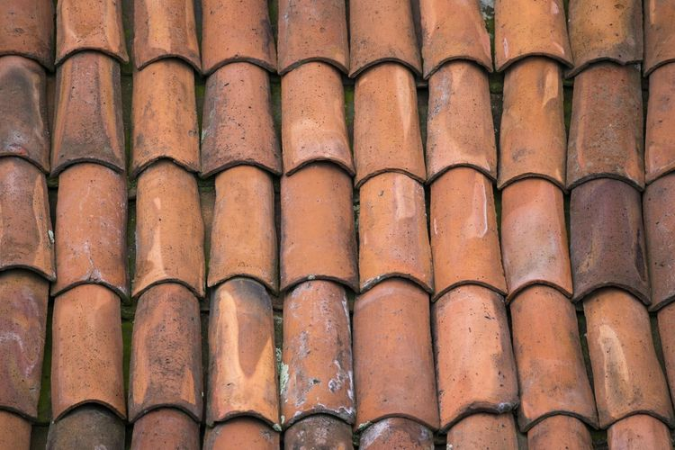 View of a roof covered with red mud tiles. Architecture Arrangement Backgrounds Brown Building Building Exterior Built Structure Close-up Day Full Frame In A Row Low Angle View No People Order Outdoors Pattern Repetition Roof Roof Tile Side By Side