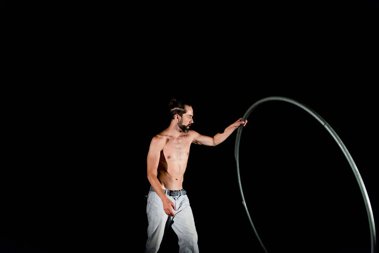 Circus Adult Black Background Chest Copy Space Holding Indoors  Looking Men Mid Adult Muscular Build One Person Shirtless Stage Standing Strength Studio Shot Three Quarter Length Young Adult Young Men