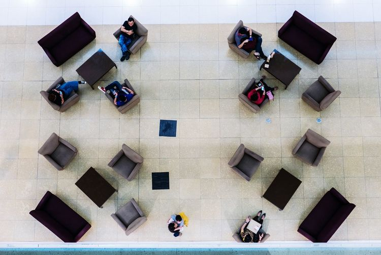 High Angle View Of People Sitting On Armchairs In Building
