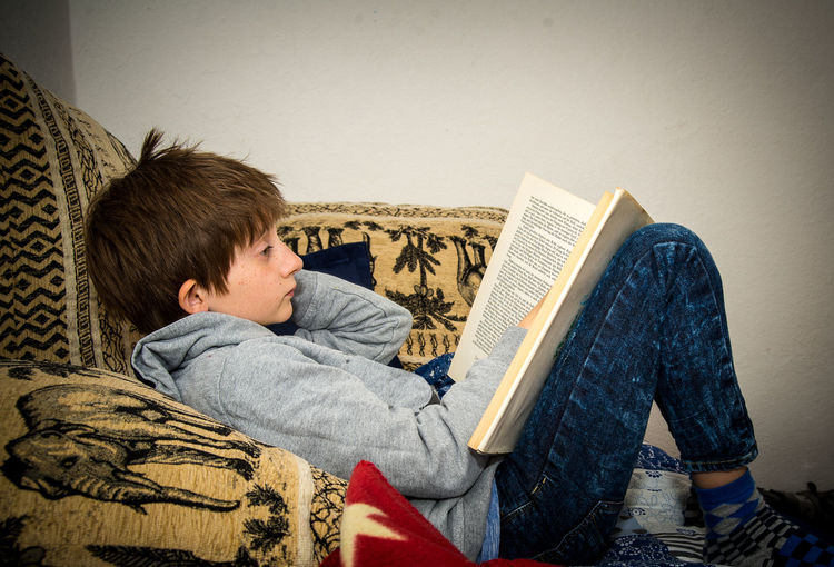 Boy reading a book at home on the day of the book Book Boys Casual Clothing Childhood Concentration Day Day Of The Book Domestic Life Education Home Interior Indoors  Learning Leisure Activity Living Room One Person Real People Relaxation Sitting Sofa