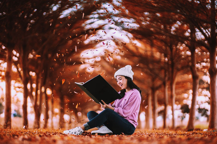 Autumn is a second spring when every leaf is a flower.🍂🍁📙 Young smiling woman read a book at the autumn leaves falling and blurry background. Nature Real People Vintage Tree Magic Winter Autumn Celebration Autumn Leaves Christmas November Book Plant Connection Lifestyles Young Adult Full Length Autumn Mood Autumn🍁🍁🍁 One Person Young Women Casual Clothing Leisure Activity Wireless Technology