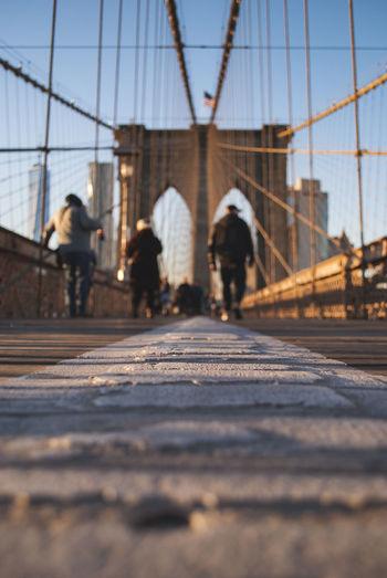 People walking on bridge against sky in city