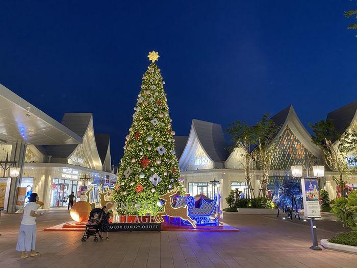 Illuminated christmas tree against blue sky
