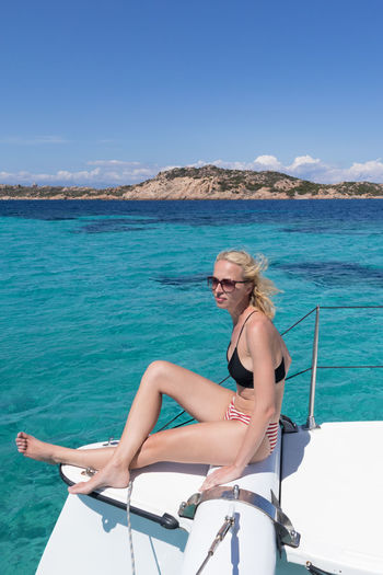 Full length of woman sitting on boat in sea against sky