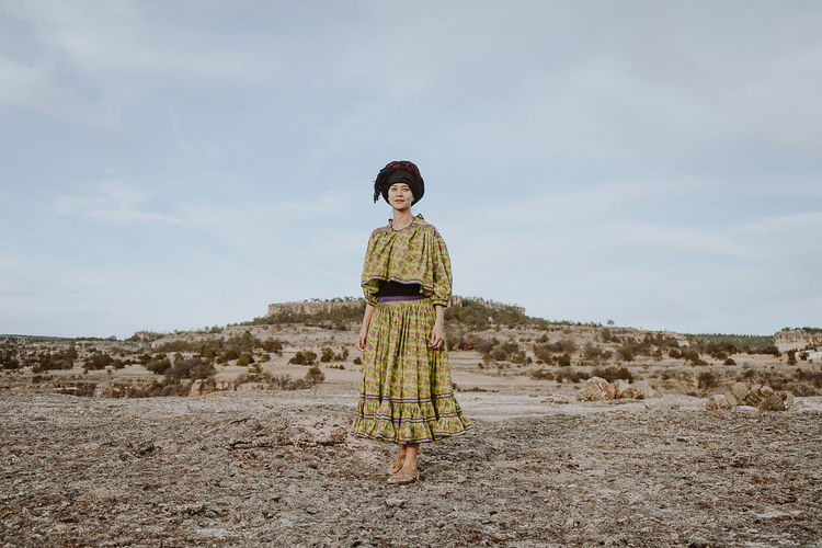 Full length of young woman standing on land against sky
