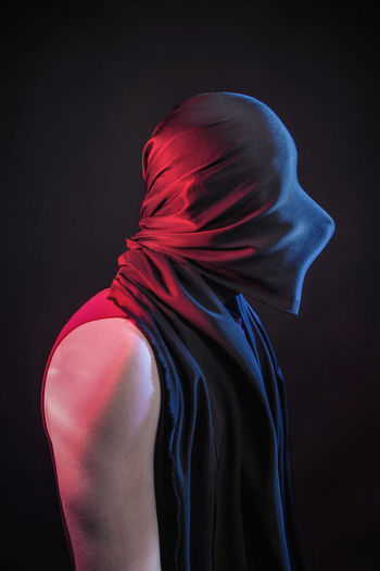 Side View Of Man Covering Face Against Black Background