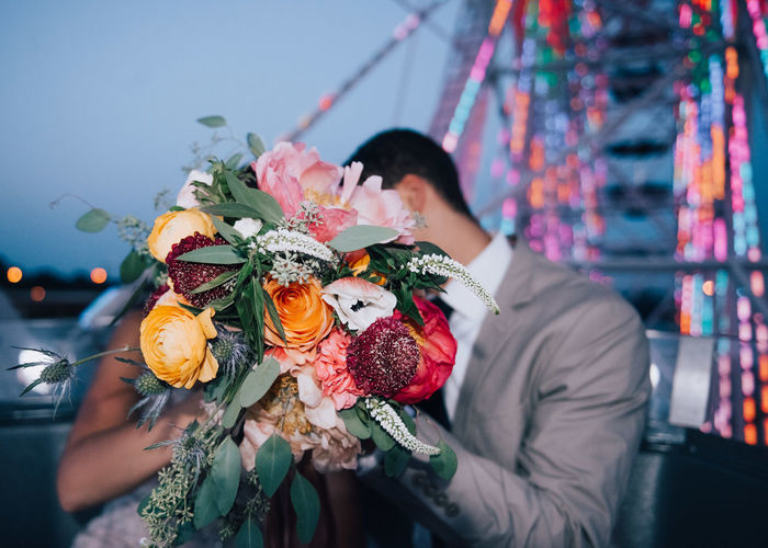 Couple Covering Face With Flower Bouquet During Wedding Ceremony