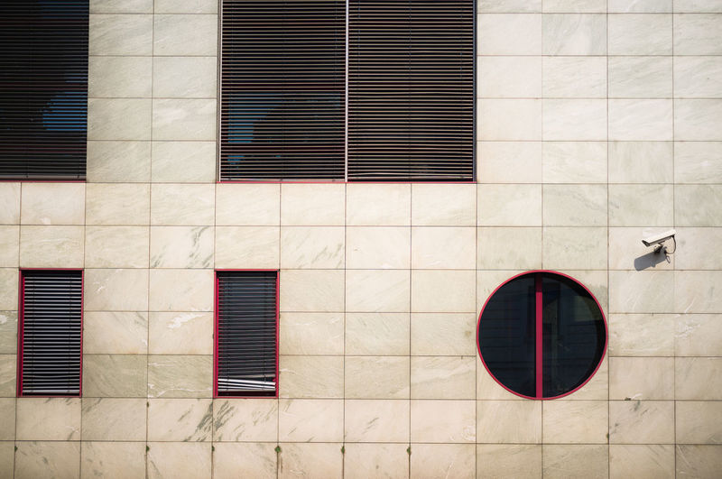 Wide tiled wall detail of geometric windows and space. Architecture Brick Wall Building Building Exterior Built Structure Circle City Closed Day Exterior Façade Geometric Geometric Shapes Modern No People Outdoors Vents