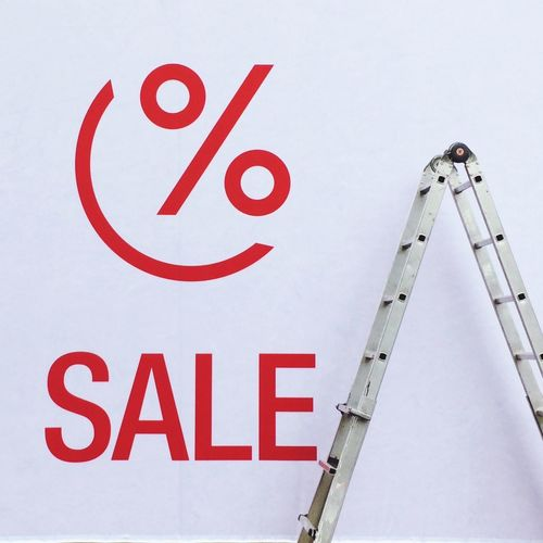Ladder by sale and percentage sign on white wall