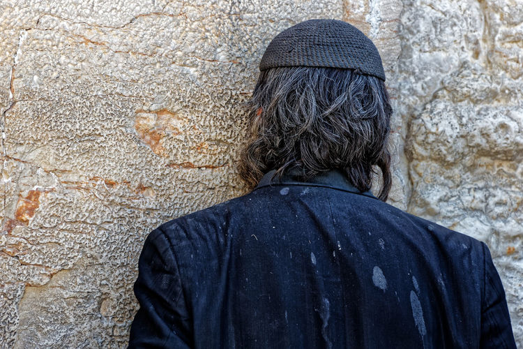 Rear View Of Man Praying On Wailing Wall