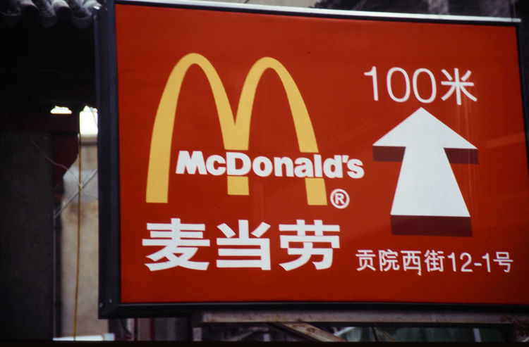 Red Day Outdoors Text Communication Close-up No People Chinese Writing A Taste Of China Red Sign Up Arrow West Meets East McDonalds Sign. Chinese McDonalds Eating In Shanghai