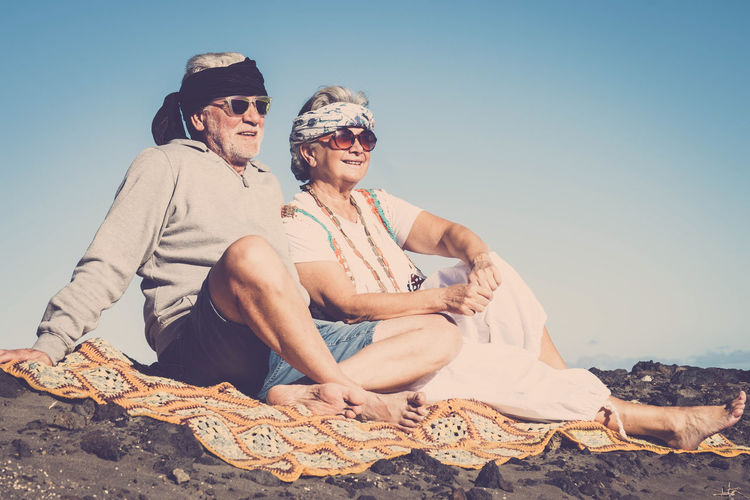 Senior Couple Wearing Sunglasses While Sitting At Beach Against Clear Sky