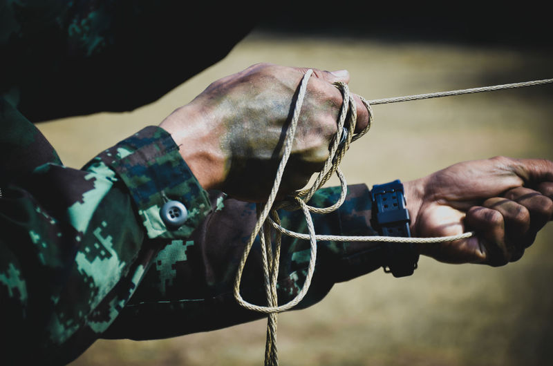 Cropped hands of army soldier pulling rope