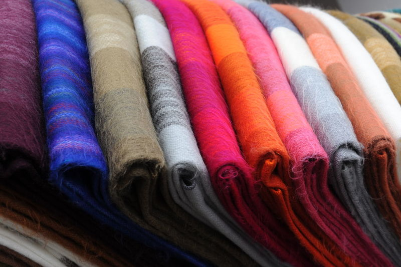 Colorful blankets arranged for sale in store