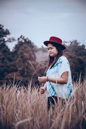 Young Woman Wearing Hat Standing On Field
