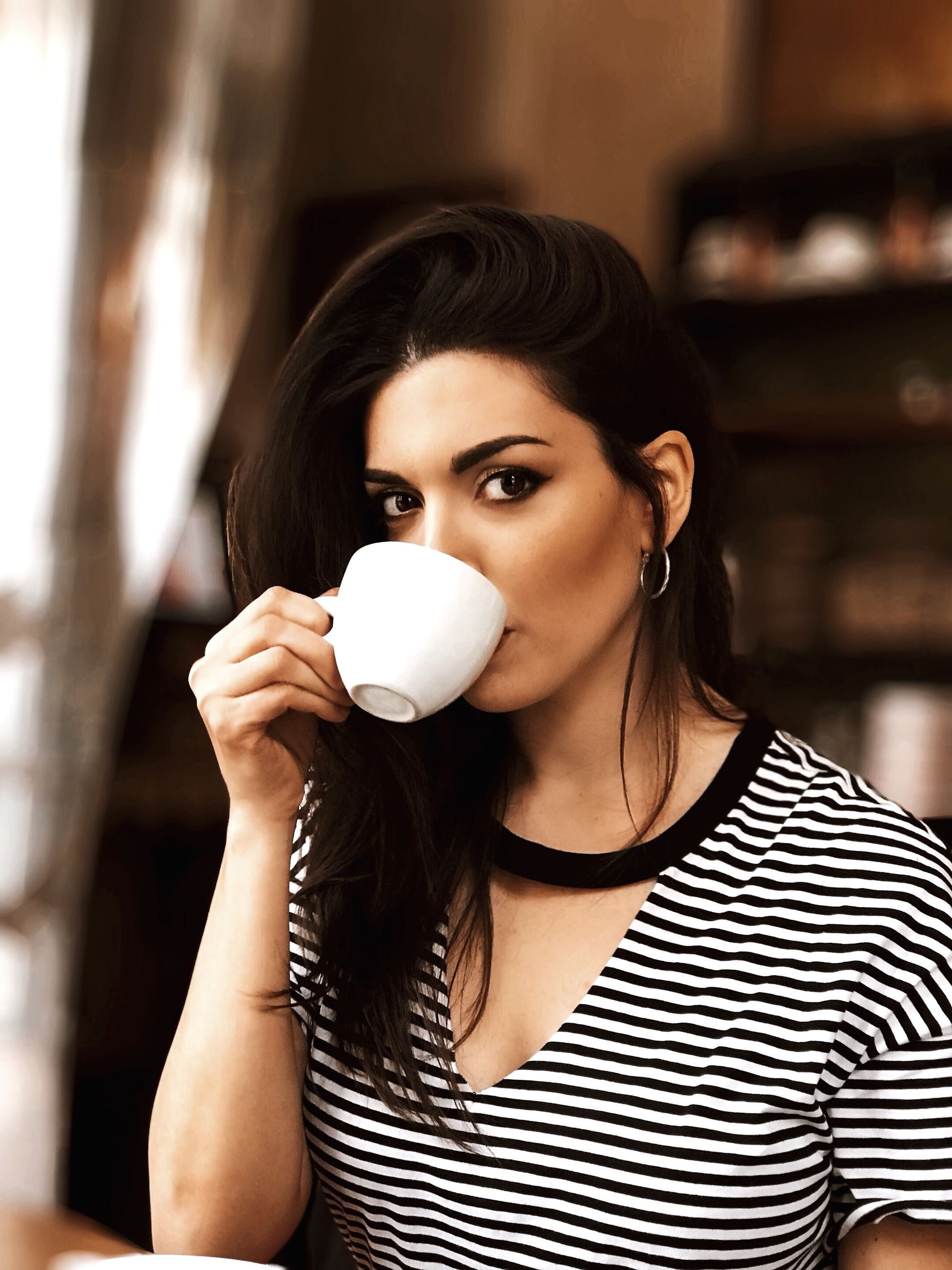 one person, young adult, indoors, young women, portrait, lifestyles, real people, front view, food and drink, focus on foreground, striped, women, holding, looking at camera, leisure activity, beautiful woman, casual clothing, beauty, adult, coffee, hairstyle, drinking