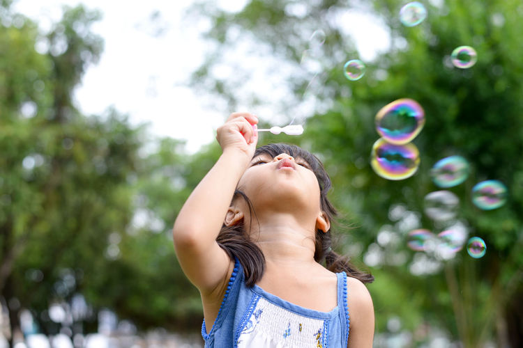 Cute girl blowing bubbles at park