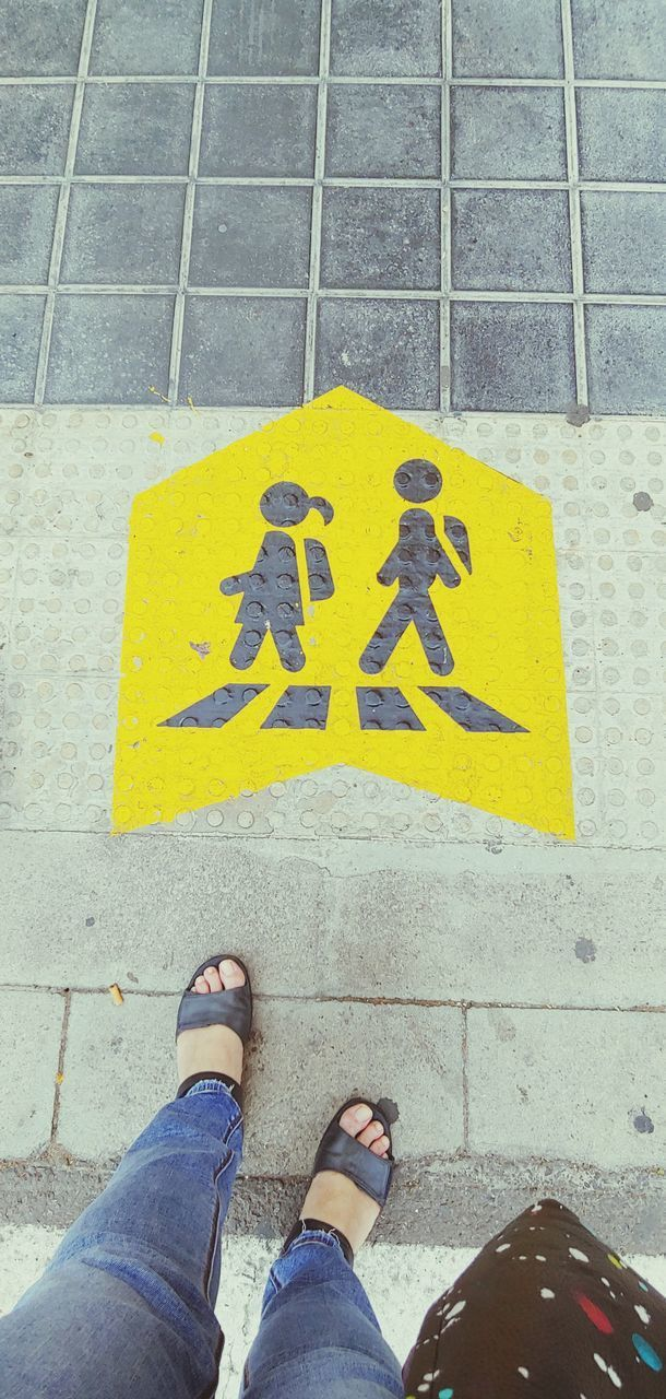 low section, human leg, personal perspective, human body part, real people, sign, body part, communication, one person, shoe, high angle view, yellow, footpath, day, lifestyles, text, men, standing, leisure activity, outdoors, guidance, human foot, flooring, jeans, paving stone