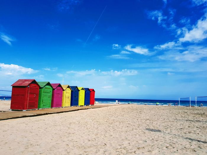 Multi colored huts at beach against blue sky