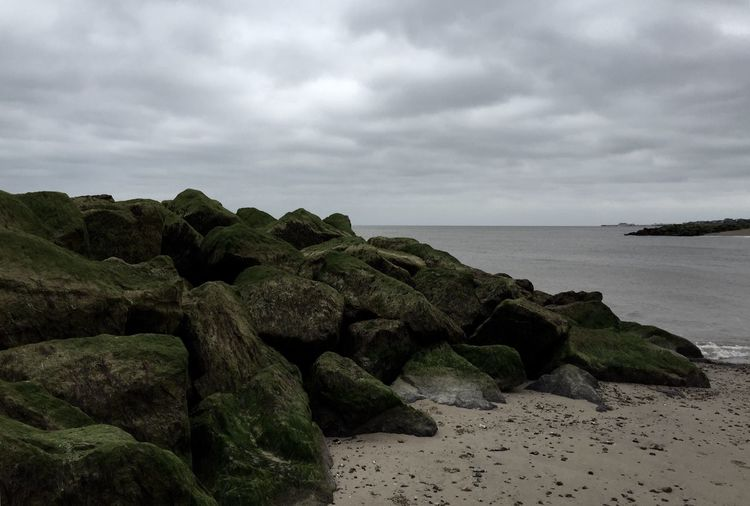Moss covered rocks on shore at beach against cloudy sky