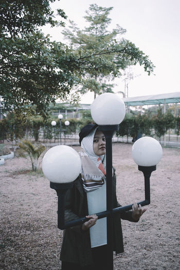Woman holding balloons with umbrella standing by trees