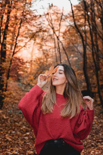 Portrait of beautiful young woman standing on land during autumn