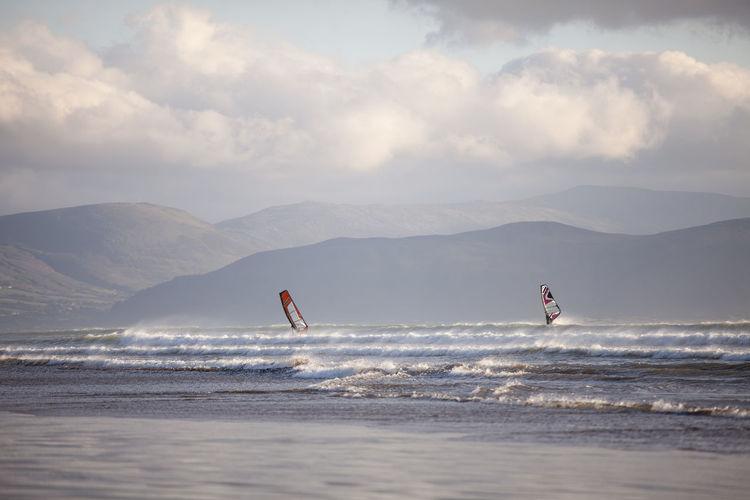 Windsurfing on beach against sky