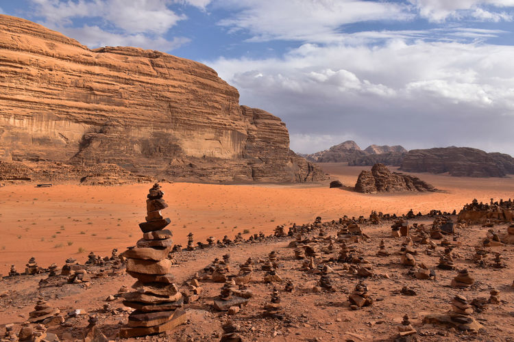 Red rock formations on wadi rum landscape against cloudy sky