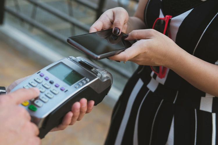 Midsection of woman making mobile payment in store