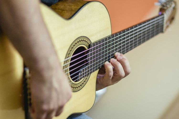 Cropped image of man playing acoustic guitar